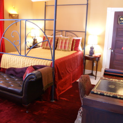 Wrought-iron canopy queen bed and chaise longue in Le Moulin Rouge suite