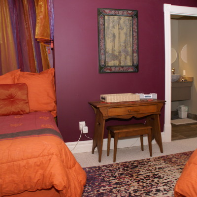 View of one of two single beds, desk and entrance to ensuite bathroom in the Sultan's Tent suite on the second floor.