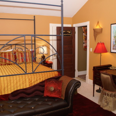 A queen bed and a chaise longue in Le Moulin Rouge suite.